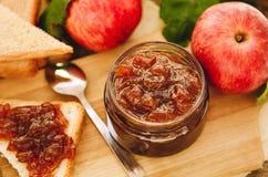 Jabłczany dżem na grzance w słoju i, świezi czerwoni jabłka na tnącej desce na drewnianym stole Wyśmienicie śniadanie, wieśniaka  fotografia royalty free
