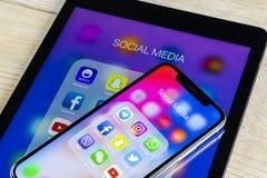 Jabłczany iPhone X i iPad z ikonami ogólnospołeczny medialny facebook, instagram, świergot, snapchat zastosowanie na ekranie Ogól obraz stock