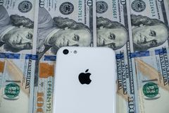 Jabłczany iphone i strategicznie umieszczający $100 rachunków fotografia stock