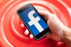 Jabłczany iPhone 7 trzymający w jeden ręce pokazuje swój ekran z Facebook logo obrazy royalty free