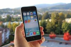 Jabłczany iPhone w mężczyzna ręce z natury tłem obraz stock