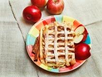 Jabłczany kulebiak z ciasto siatką, cukieru proszkiem na Ceramicznym talerzu z cynamonem i kawałkami Świeży Apple, Odgórny widok Obraz Stock