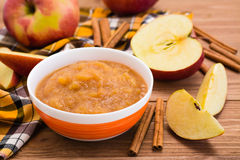 Jabłczany puree, jabłka i cynamon na drewnianym stole, fotografia stock
