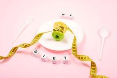 Jabłczany sedno z pomiarową taśmą zamiast talii na białym talerzu z tekstem MÓJ dieta na różowym tle Dieta, ważenie strata, obraz royalty free