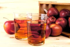 Jabłczany sok i świezi jabłka w drewnianym pudełku zdjęcia royalty free