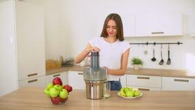 Jabłczany sok - kobiet juicing jabłka, pić je świeżego w kuchni daje aprobatom w domu i warzywa i sok zbiory
