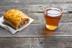 Jabłczany strudel na drewnianej desce słuzyć z herbatą obraz royalty free