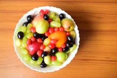Jabłczanych winogron pomarańczowy śliwkowy aranżer wpólnie w porecelin pucharze jako zdrowa dieta fotografia royalty free