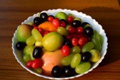 Jabłczanych winogron pomarańczowy śliwkowy aranżer wpólnie w porecelin pucharze jako zdrowa dieta obrazy royalty free