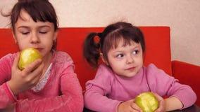 jabłek dzieci target2076_1_ Dwa siostry je żółtych jabłka podczas gdy siedzący na pomarańczowej leżance zbiory