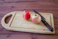 Jabłka i kuchenny nóż na tnącej desce Obraz Royalty Free