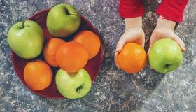 Jabłka i pomarańcze w rękach dziecko fotografia royalty free