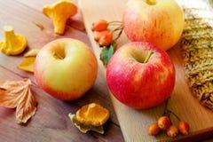 Jabłka na drewnianym stole nad jesieni bokeh tłem fotografia stock