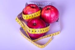 Jabłka z pomiarową taśmą na białym tle Obrazy Stock