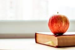 Jabłko na czerwonej książce blisko okno Enpty przestrzeń dla teksta zdjęcie royalty free