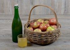 Jabłczany kosz i butelka z szklanym cydrem Fotografia Royalty Free