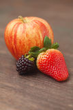 jabłko, czernica i truskawka na drewnianej powierzchni, Obraz Royalty Free