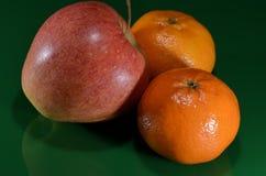Jabłko i dwa tangerines na zieleni ziemi Obrazy Royalty Free