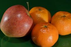 Jabłko i trzy tangerines na zieleni ziemi Fotografia Royalty Free