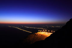 Jabel hafeet. Jebel Hafeet is a mountain primarily in the United Arab Emirates on the outskirts of Al Ain. The mountain actually straddles part of the border Stock Photo