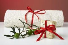 Jabón verde oliva hecho a mano con la rama de olivo y una toalla, como regalo. Foto de archivo