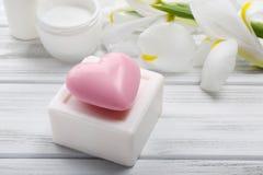 Jabones y crema cosmética con las flores hermosas en la tabla de madera, Fotografía de archivo libre de regalías
