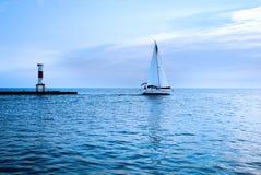 Jacht bij de zonsondergang in het blauwe overzees Wit zeil tegen de rug stock fotografie