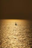 Jacht die op water van oceaan bij zonsondergang varen stock afbeeldingen