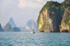 Jacht en catamaran in het overzees onder de rotsachtige eilanden Stock Afbeelding