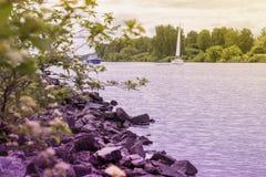 Jacht en schip op achtergrond van meer, tegenover kust De zomermeer, strand met stenen, de Zomerlandschap Seizoenen, ecologie Stock Foto