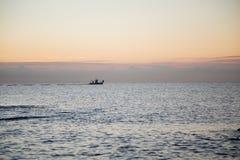 Jacht in het overzees bij zonsondergang Stock Afbeelding