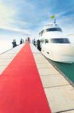 Jacht kurtyzacja przy molem z czerwonym chodnikiem bawić się Zdjęcie Royalty Free