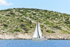 Jacht met wit zeil dichtbij de kust van Dalmatië Stock Afbeelding