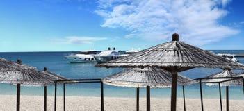 Jacht op het strand met paraplu's wordt vastgelegd die royalty-vrije stock afbeeldingen