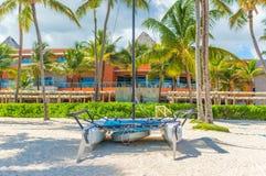 Jacht op het strand onder palmen stock afbeelding