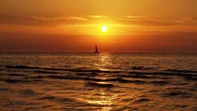 Jacht op overzees en oranje wolken bij zonsondergang Stock Foto's