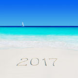 Jacht pod żaglem przy plaży i roku piaska 2017 podpisem Obraz Stock
