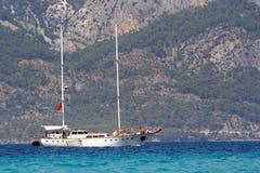 Jacht tegen bergachtige Turkse kust Royalty-vrije Stock Fotografie