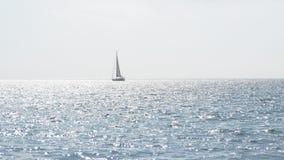 Jacht z żaglami w spokojnej błękitne wody morze Żaglówka na horyzoncie w pięknym krajobrazie gdy tło błękitny był łódkowate łodzi Zdjęcie Stock