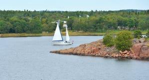 Jacht z białym żaglem wśród skalistych wysp w morzu bałtyckim Obrazy Royalty Free