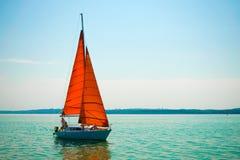 Jacht z czerwienią żegluje przeciw niebieskiemu niebu Żaglówka z szkarłatem zdjęcie stock