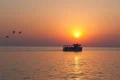 Jacht z turystami przy zmierzchem z ptakami lata daleko od obraz royalty free