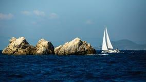Jachtboot met witte zeilen dichtbij de rotsen in het Egeïsche overzees Reis royalty-vrije stock afbeeldingen