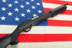 Jachtgeweer over de vlag van de V.S. als symbool van tweede amendement stock afbeelding