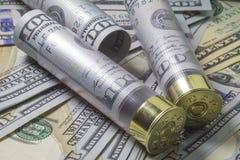 Jachtgeweershells laadden met honderd ons dollarbankbiljetten op de verschillende achtergrond van de dollarrekeningen van de V.S. Stock Foto's