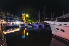 Jachthaven met jachten en boot bij de nacht stock foto's