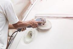 Jachtonderhoud Een mens het oppoetsen kant van de witte boot in royalty-vrije stock foto