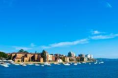 Jachty i żaglówki zakotwiczają wzdłuż miasto brzeg pod jasnym b Obrazy Royalty Free