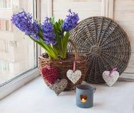 Jacintos en una cesta, corazones decorativos y una vela Foto de archivo