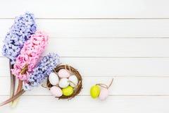 Jacintos frescos y huevos de Pascua decorativos en pequeña jerarquía en la tabla blanca Visión superior Fotos de archivo libres de regalías